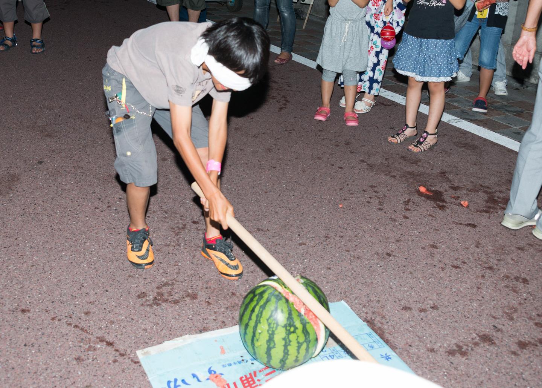 japanischer Junge mit verbundenen Augen zerschlägt Wassermelone bei einem Fest