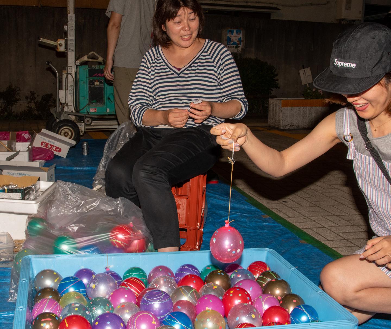 Frau angelt Luftballon aus Becken mit Wasser