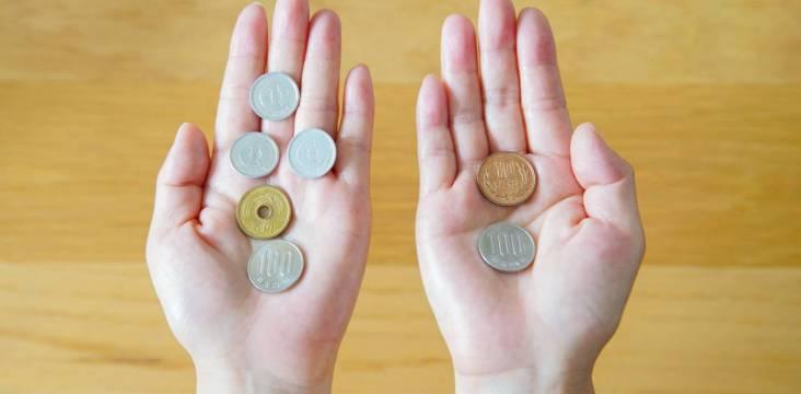 Zwei offene Hände halten Yen-Münzen