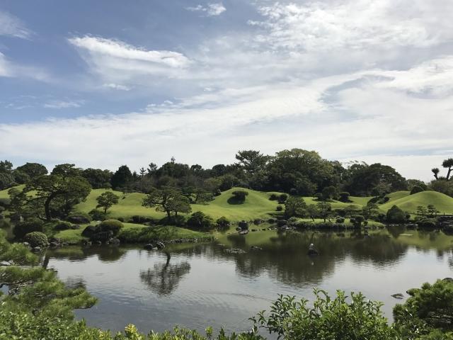 Japanischer Hügelgarten mit Teich im Vordergrund