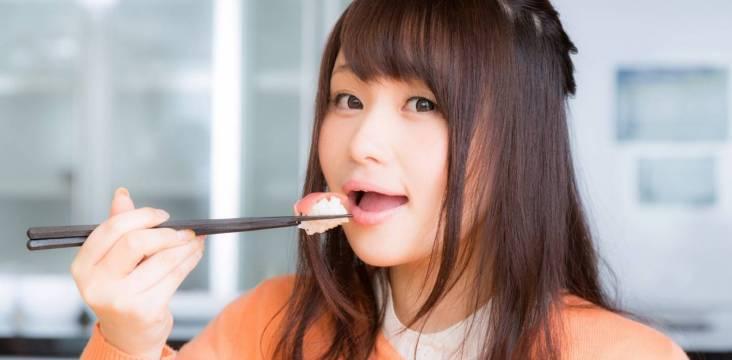 junge Frau beim Sushi essen