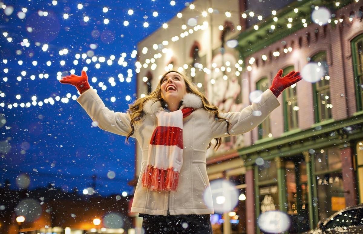 Frau vor weihnachtlich dekorierten Häusern