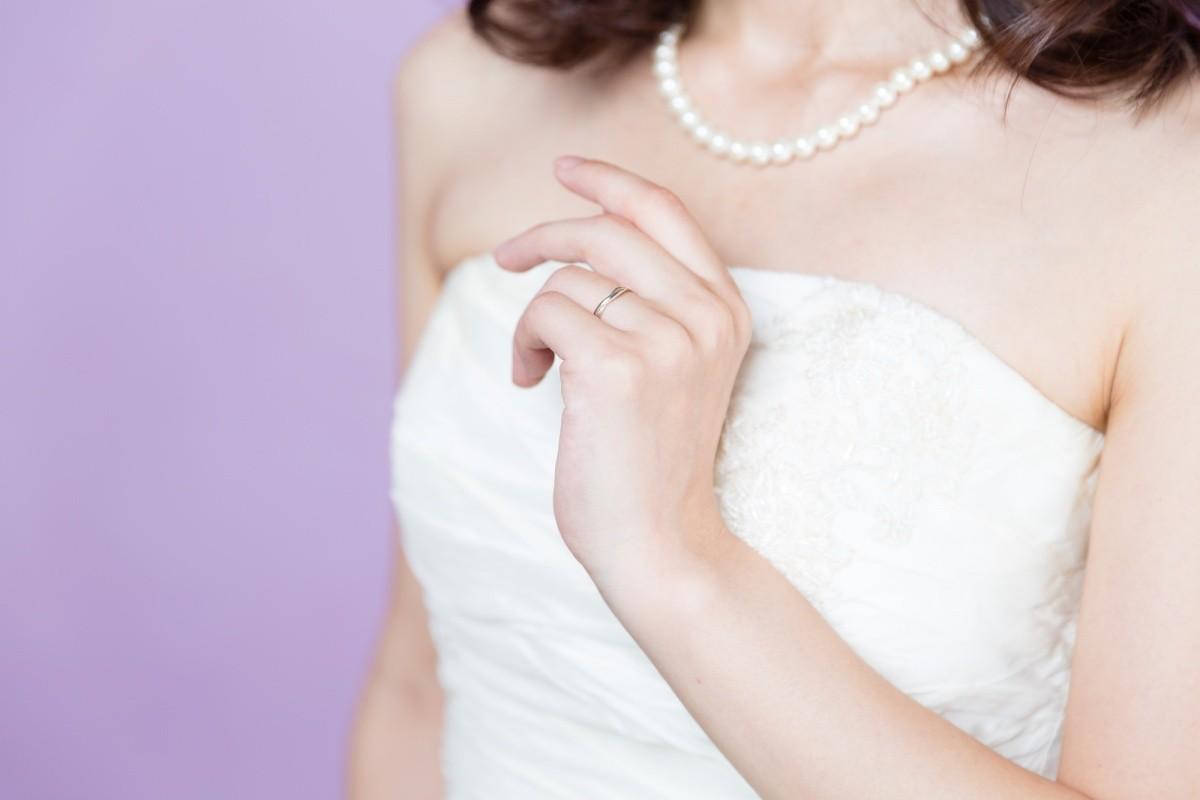 Oberkörper einer Frau mit Perlenkette und weißem Kleid