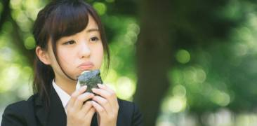 Eine Frau isst Onigiri im Park.