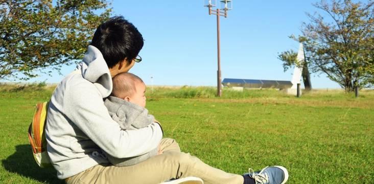 Vater auf einer Wiese mit Baby im Arm
