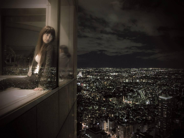 Japanische Frau, die bei Nacht aus einem Hotelfenster auf das Stadtpanorama schaut