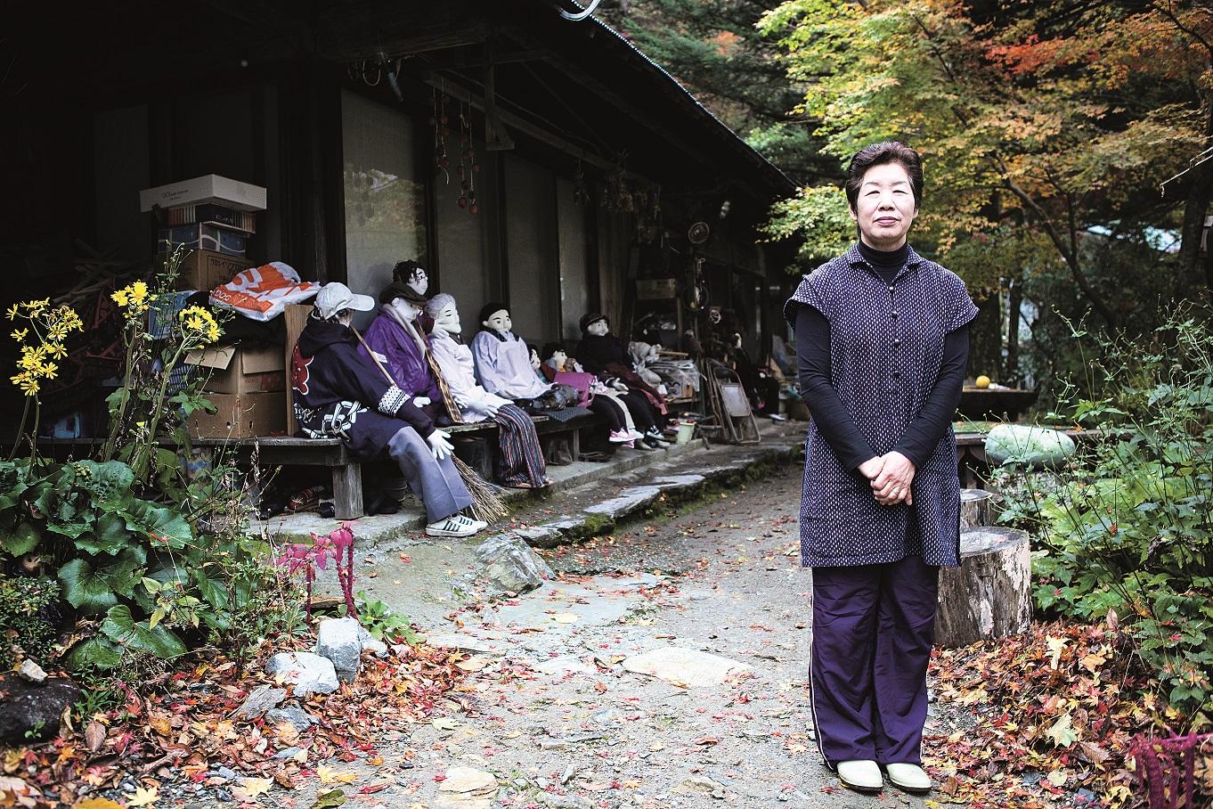 Puppenmacherin Tsukimi Ayano aus dem Dorf Nagoro vor ihrem Haus mit Puppen im Hintergrund