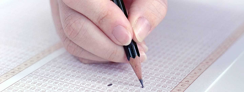 Hand, die einen Prüfungsbogen ausfüllt