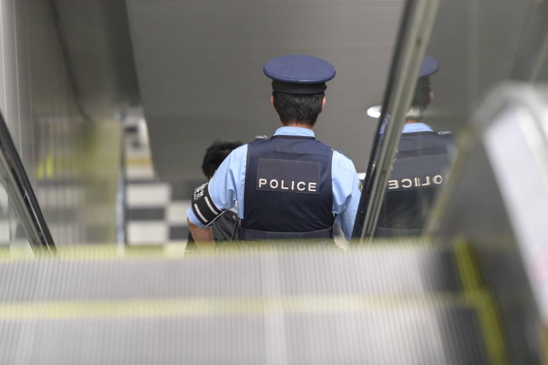 Japanischer Polizist auf einer Bahnhofs-Rolltreppe