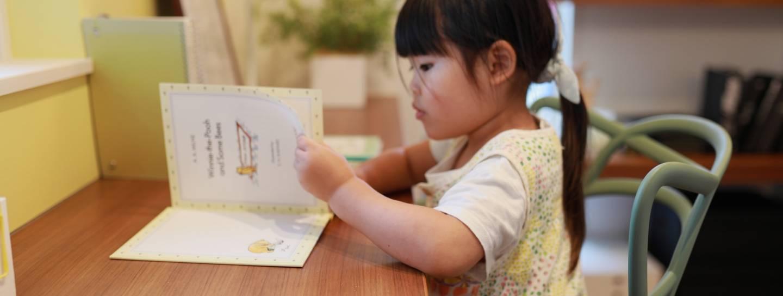 Kleines Mädchen, dass am Schreibtisch in einem Kinderbuch blättert