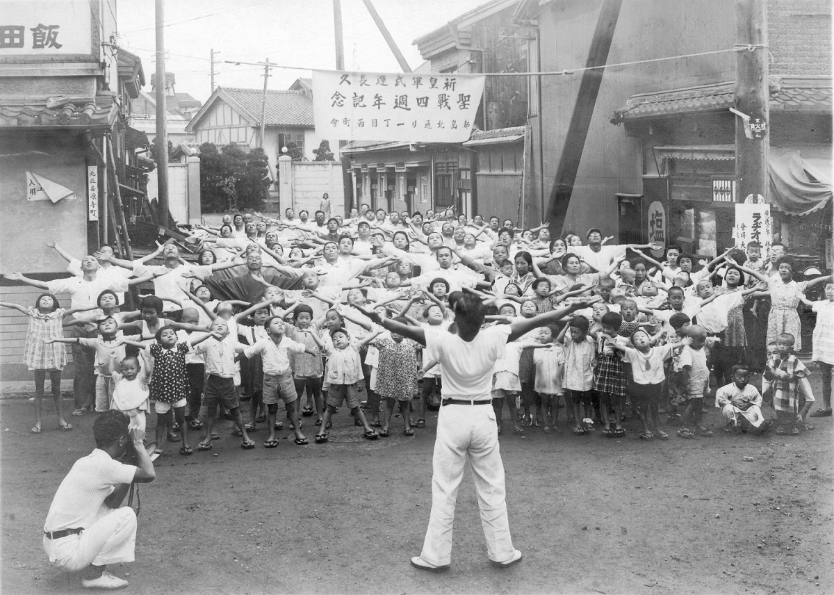 Gruppe von Kindern und Erwachsenen bei der Radiogymnastik (Zweiter Weltkrieg)