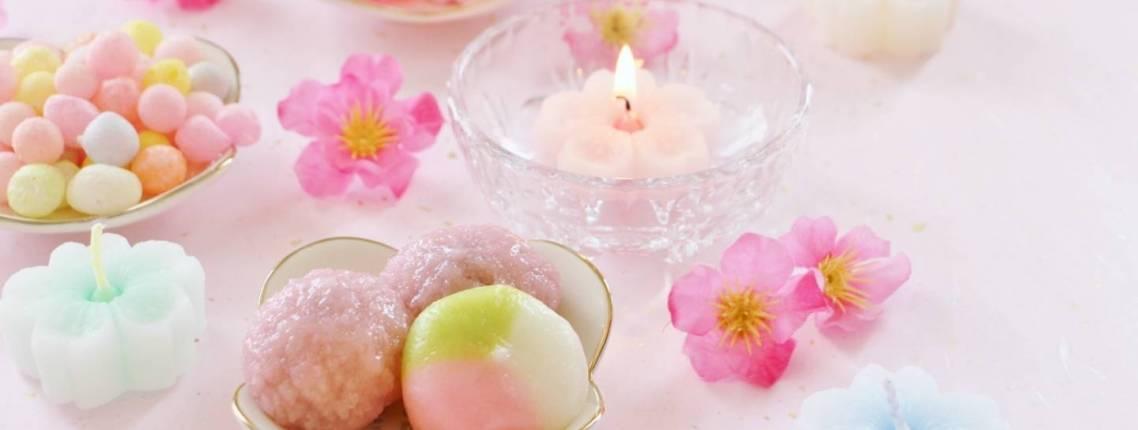 Süßigkeiten, Blumen und Kerzen zum Hina Matsuri (Mädchenfest)