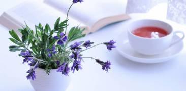 Blumenstrauß, Tee und aufgeschlagenes Buch