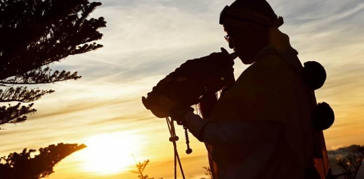 Ein Shugenja bläst ein Muschelhorn im Sonnenaufgang