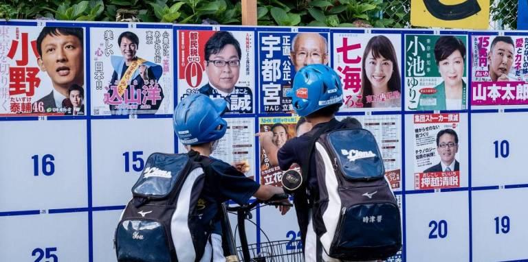 05. Juli 2020: Teenager schauen auf Wahlplakete verschiedener Kandidaten in Tokyo.