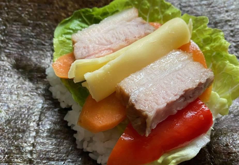 Fleisch, Käse, Gemüse und Reis auf Algenblatt