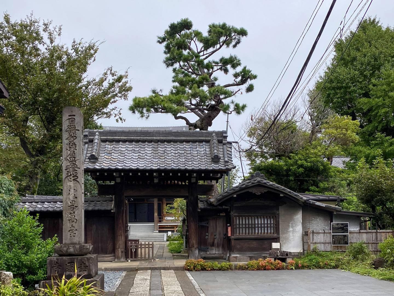 Vor dem Tempel Kōkoku-ji, lange gepflasterter Weg, überdachtes Holztor