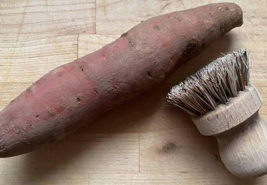 Ungeschälte Süßkartoffeln auf Holztisch, Bürste mit Holzgriff