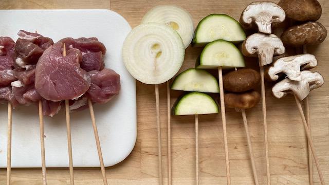 Rohes Fleisch, Gemüse und Pilze auf Holzspießen