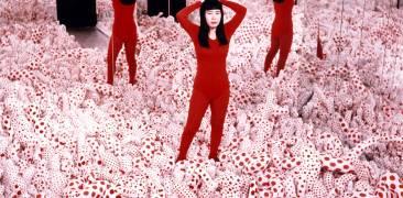 Künstlerische Installation von Kusama Yayoi in einem Spiegelraum mit rotem Kostüm und Polka Dots