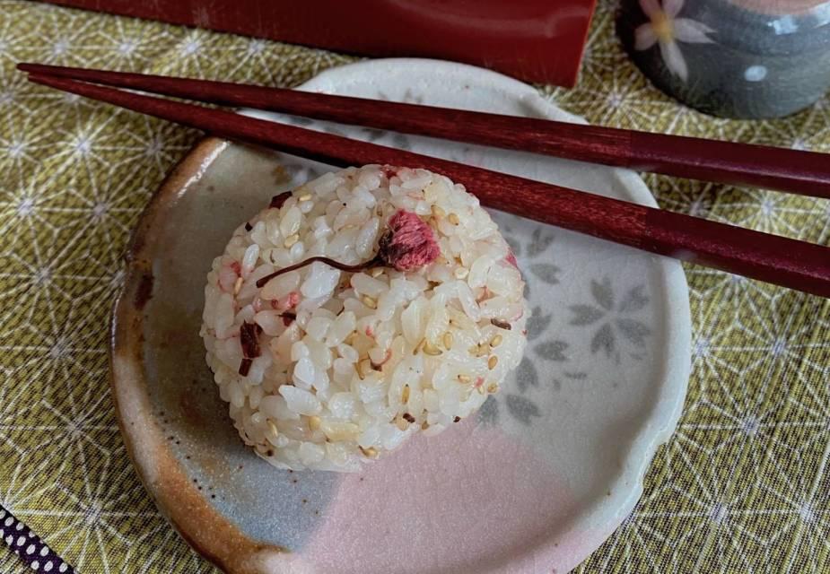 Reisbällchen mit Kirschblüten auf Tellereben mit Essstäbchen