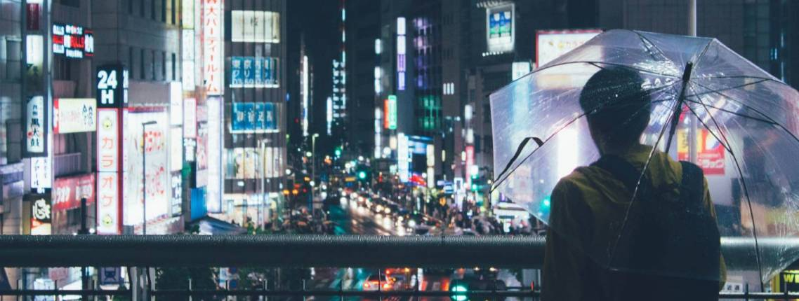 Mann mit Regenschirm blickt auf die Lichter von Shinjuku