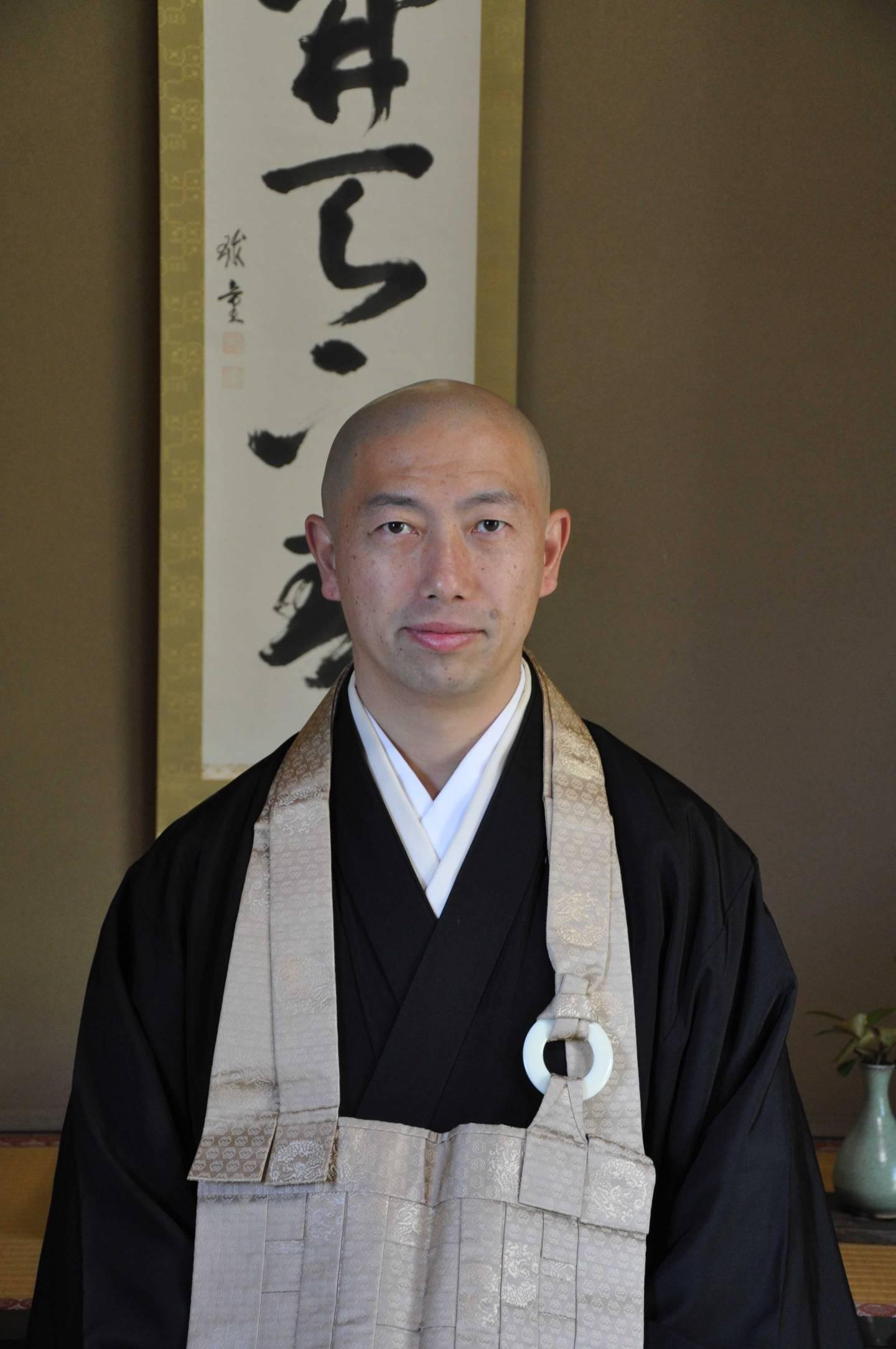 Hirai Shōshū, der Hauptpriester des Zenshōan-Tempels in Tōkyō vor einer Kalligraphie.