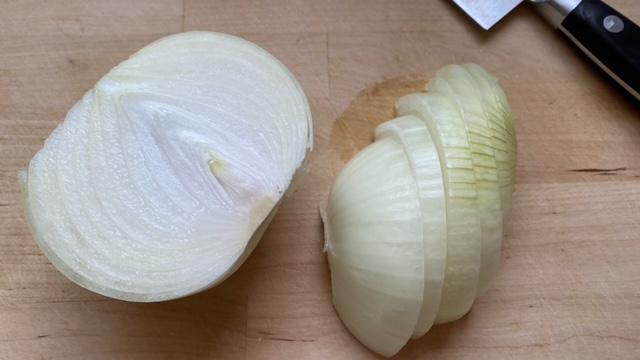 Zwiebel wird halbiert und in dünne Scheiben geschnitten