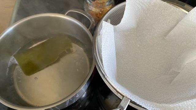 Kombu in einem Topf kaltem Wasser und mit Küchenpapier ausgelegtes Sieb