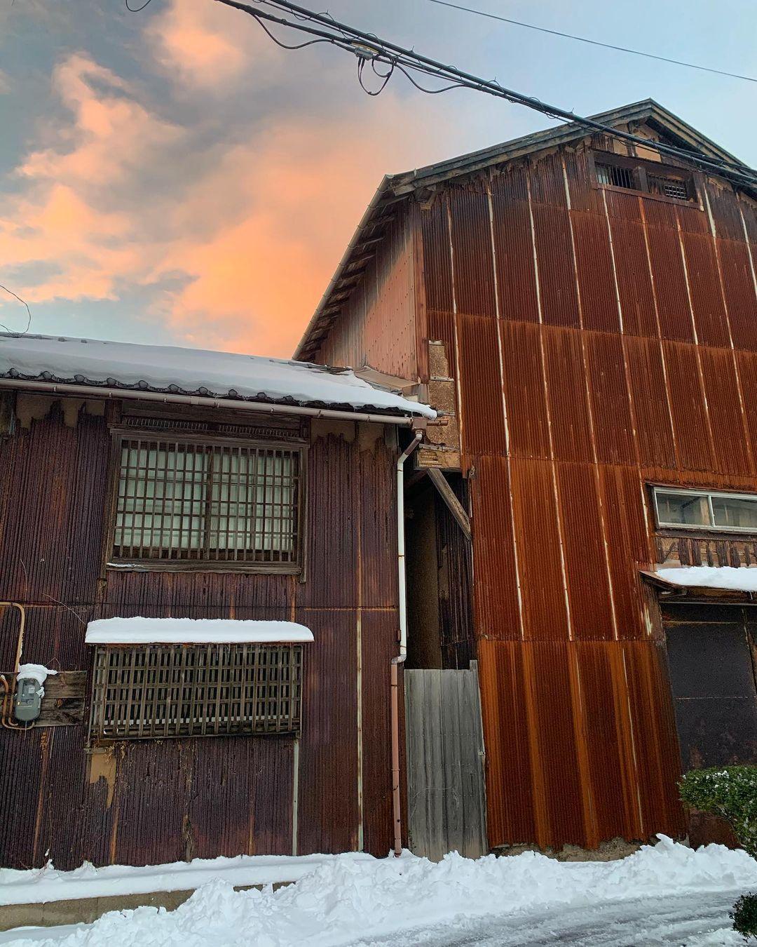 Alte Häuser in typischer, rostbrauner Farbe vor rötlichem Himmel in Aoya