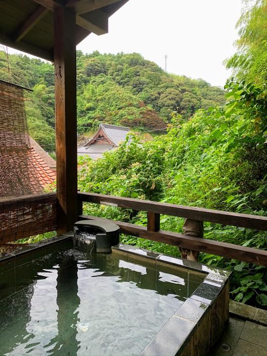 Morgenbad in Yunotsu, grüne Bäume im Hintergrund, die sich im klaren Wasser des rechteckigen Beckens spiegeln