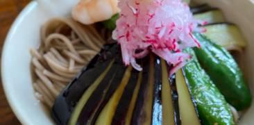 Kalte Doba-Nudeln mit Aubergine, Ingwer und Bonmot-Flocken in einer Schüssel mit Stäbchen angerichtet