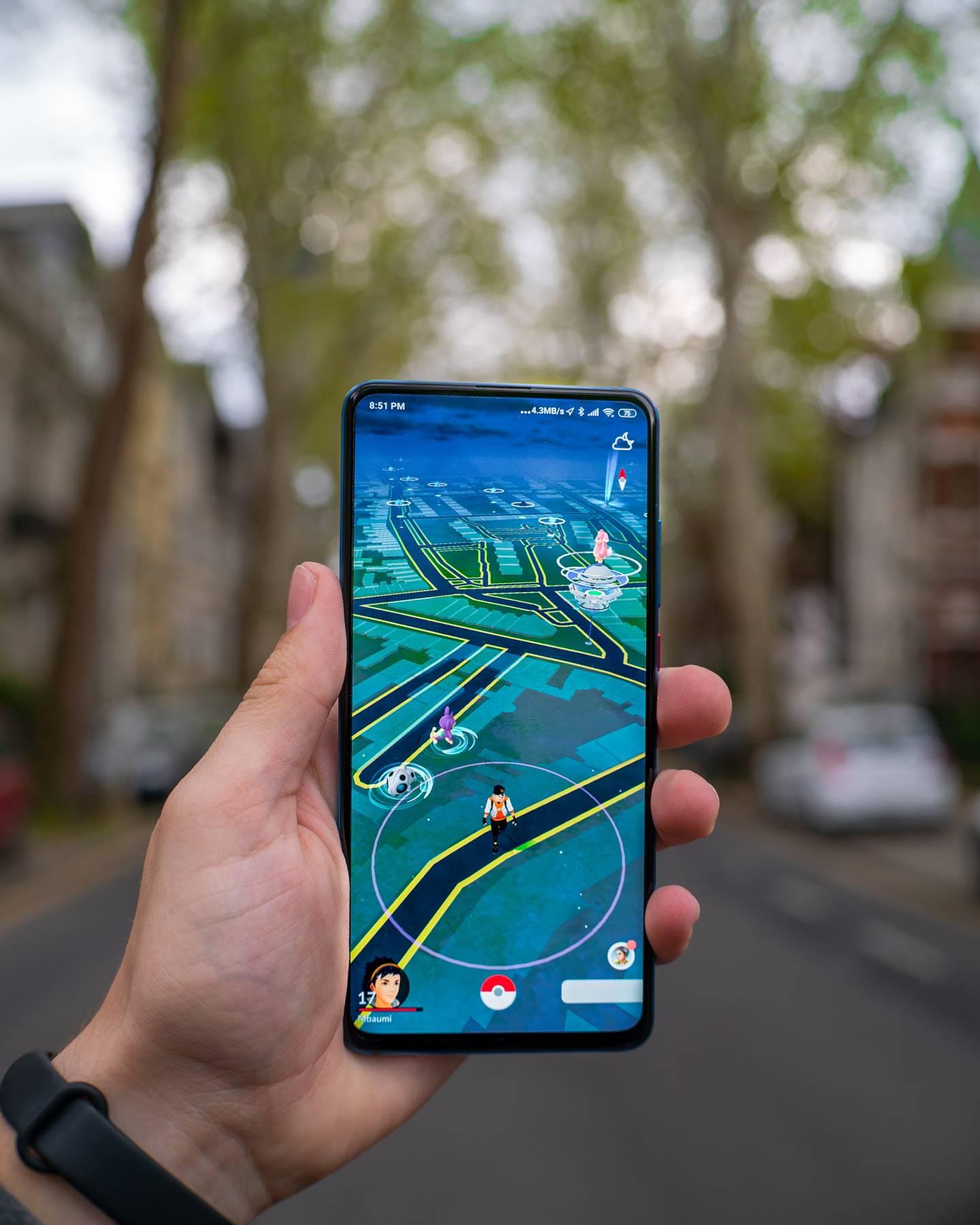 Frau Hält Smartphone mit dem Spiel Pokémon Go in die Luft, Straße mit Bäumen im Hintergrund