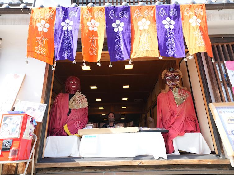 Ladengeschäft in Arimatsu mit orange- und lilafarbenen Tüchern und traditionellen roten Puppen vor dem Eingang