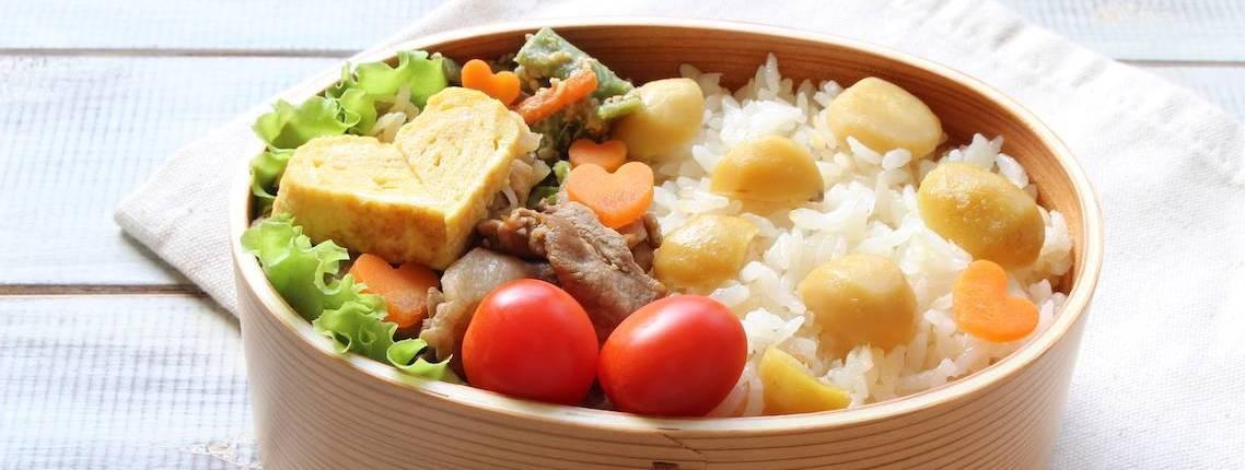 Bento-Box mit Rührei in Herzform, Salat, Tomaten und Reis mit Kastanien