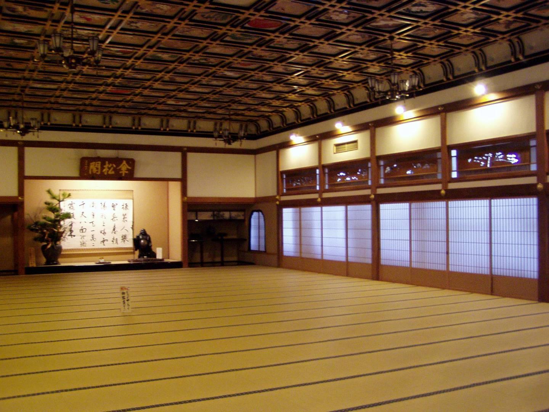 Haupthalle des Zen-Tempels Eihei-ji in Fukui mit Tatami-Fußboden und Kalligraphie an der Wand, goldbraunes Licht
