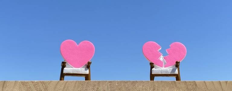 Zwei rosa Herzen in Sesseln vor blauem Himmel