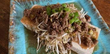 Mungbohnen auf Tofu angerichtet mit Hackfleisch und Frühlingszwiebeln auf türkisem, eckigem Teller