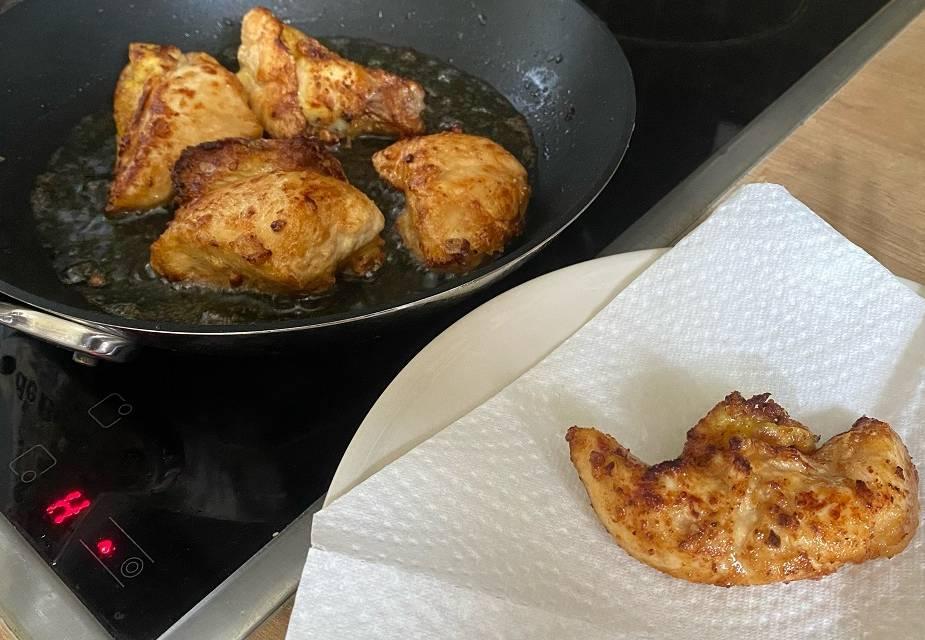 Hähnchenbruststücke werden mit Stäbchen aus der Pfanne genommen und auf Küchenpapier gelegt